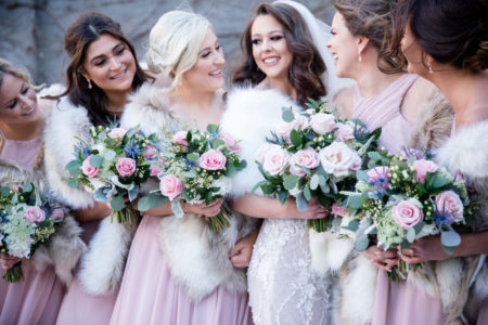 Bridal party with bouquets of pink flowers and greenery
